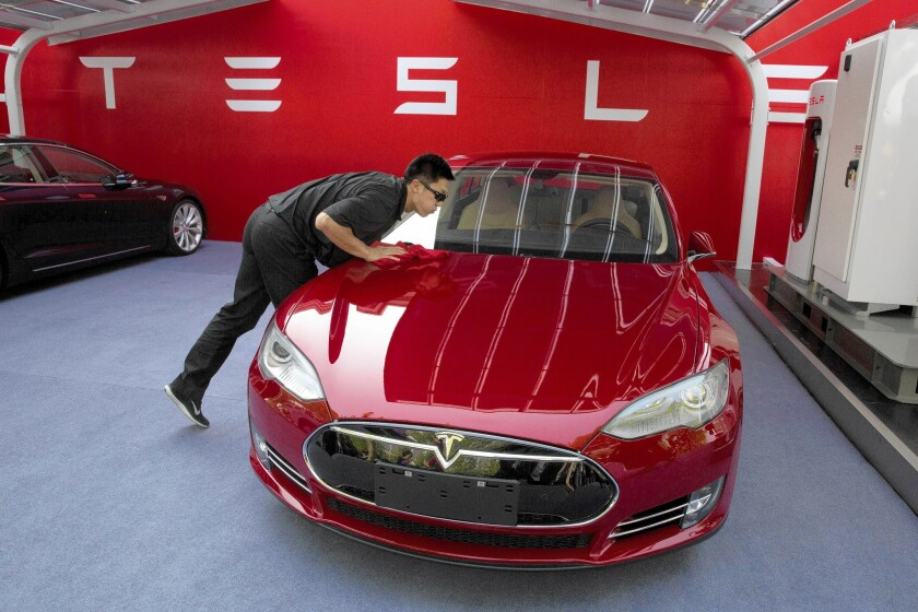 A worker cleans a Tesla Model S sedan in Beijing.