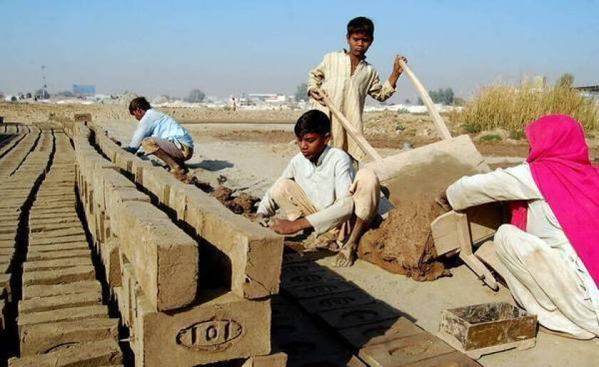 In Multan, Pakistan, Shahbaz, 10, unloads a cart of mud that will be made into bricks by his mother, Nazira Bibi, brother Shahzad and father, Mohammed Sadiq.