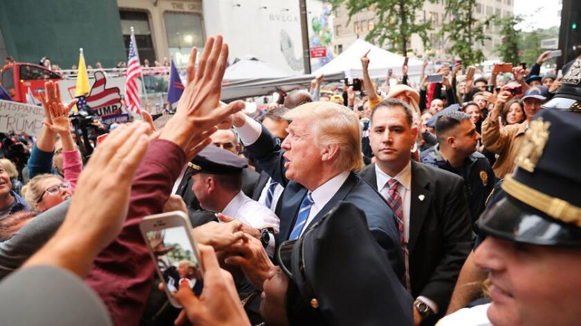 El candidato presidencial Donald Trump, en el exterior de la Trump Tower, en Nueva York, este sábado, saluda a sus fans mientras los líderes del partido republicano abandonan su campaña (Getty Images North America).