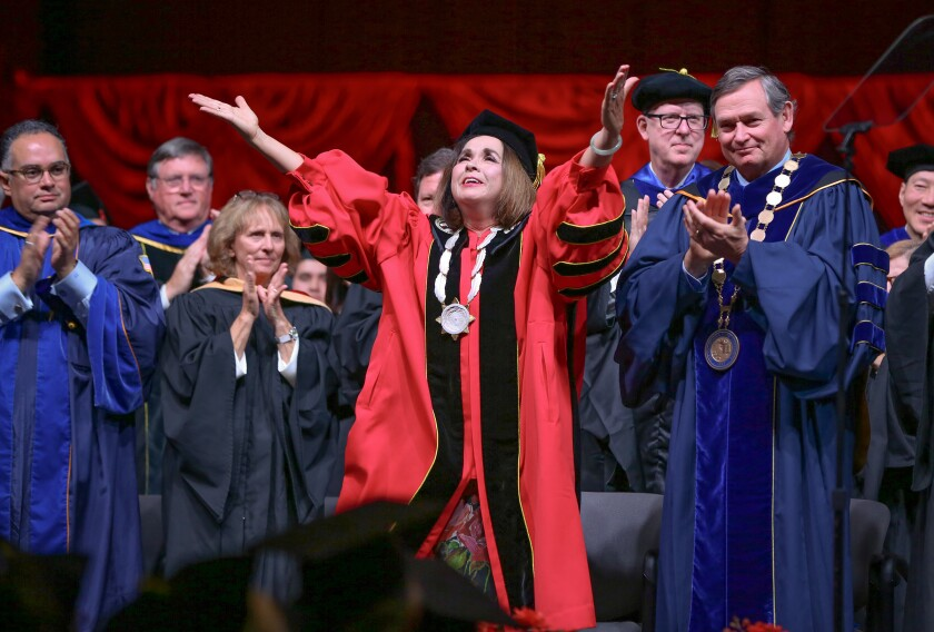 Adela de la Torre, president of San Diego State University, concludes her presidential address with outstretched arms and by blowing kisses to those in attendance to watch her be inaugurated on April 11, 2019.