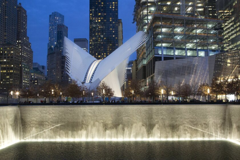 FILE - In this Dec. 11, 2015, file photo, the World Trade Center Transportation Hub, center, overlooks the September 11 Memorial north reflecting pool in New York. When it opens in early March of 2016, the hub will connect visitors to 11 different subway lines, the PATH rail system, Battery Park City Ferry Terminal, the World Trade Center Memorial Site, WTC Towers 1, 2, 3, and 4, the World Financial Center and the Winter Garden. (AP Photo/Mark Lennihan, File)