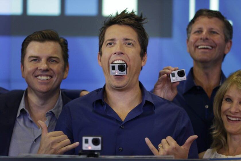 GoPro Chief Executive Nick Woodman, center, is shown at the New York Stock Exchange after the company's June 2014 initial public offering. He hasn't had so much to smile about lately.