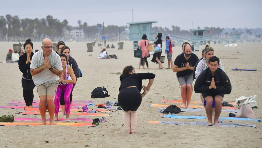 Yoga instructor Vee Gomez leads a beach yoga class on an overcast evening in Santa Monica on June 21 to celebrate International Yoga Day, which is also the summer solstice.