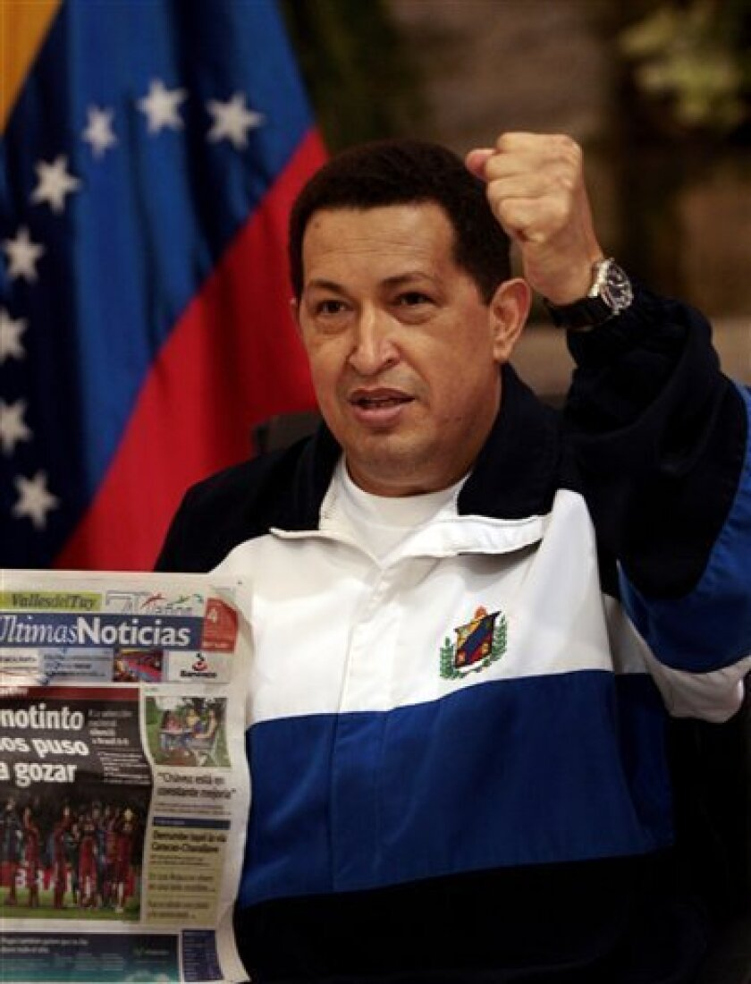 Venezuela's President Hugo Chavez raises a fist as he holds a copy of a Venezuelan newspaper at the Maiquetia Airport near Caracas, Venezuela, Monday July 4, 2011. Chavez returned to Venezuela from Cuba on Monday morning, stepping off a plane hours before dawn and saying he is feeling better as he recovers from surgery that removed a cancerous tumor. (AP Photo/Ismael Francisco, Prensa Latina)
