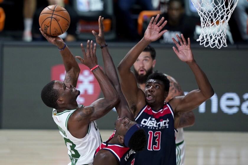 Boston Celtics' Javonte Green, left, heads to the basket past Washington Wizards' Isaac Bonga and Thomas Bryant (13) during the second half of an NBA basketball game Thursday, Aug. 13, 2020 in Lake Buena Vista, Fla. (AP Photo/Ashley Landis, Pool)