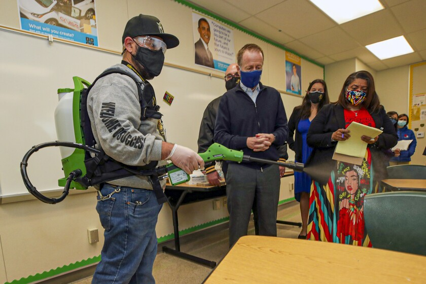 School district officials in a classroom watch a man in protective equipment spray aerosol from a device.