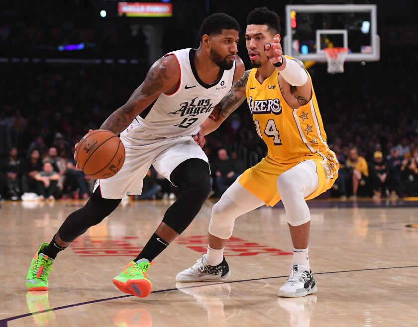 Clippers forward Paul George tries to drive past Lakers guard Danny Green during a game on Dec. 25, 2019.
