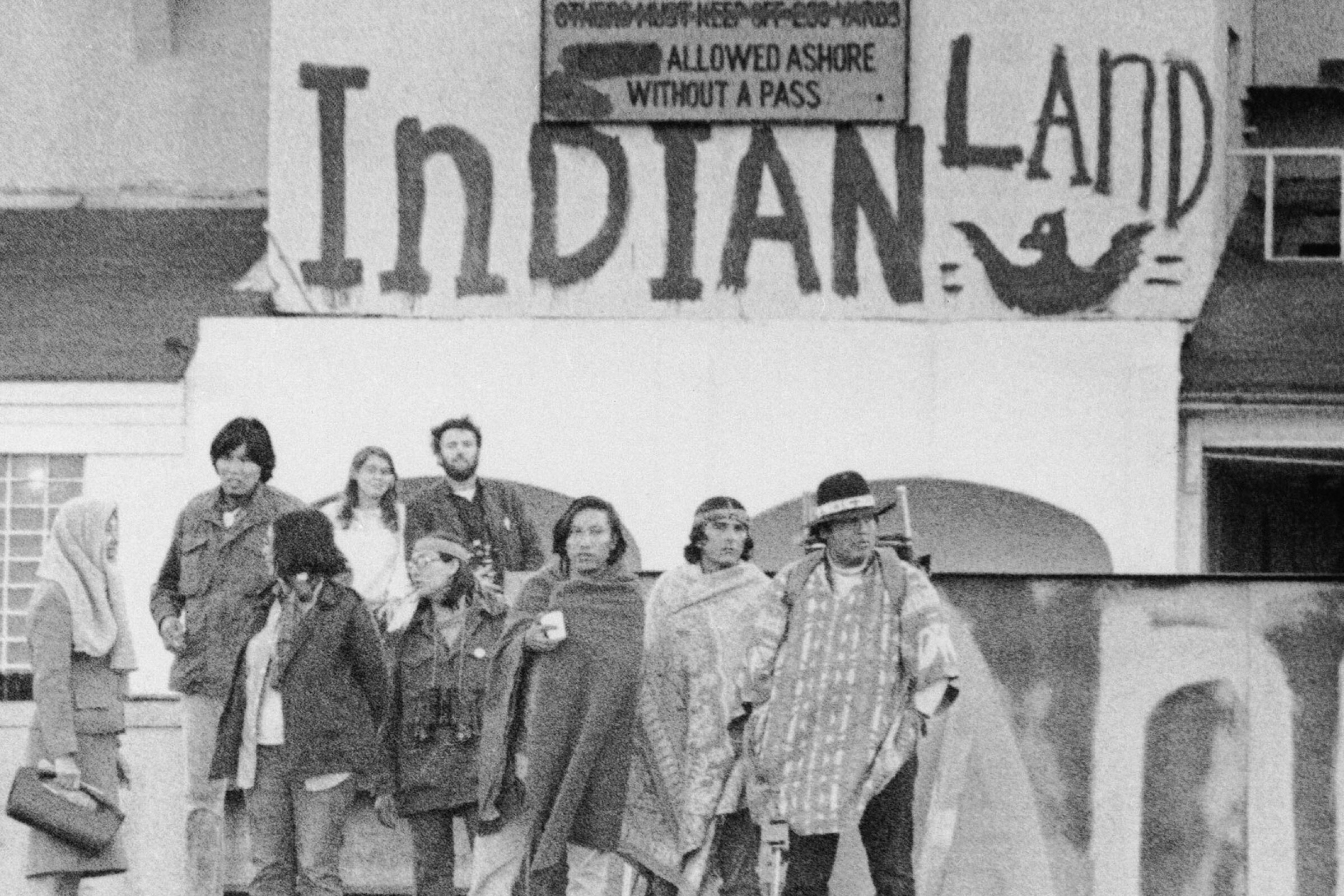 "A group of Indigenous people stand on the dock at Alcatraz under signs that read ""Indians Welcome"" and ""Indian Land"""