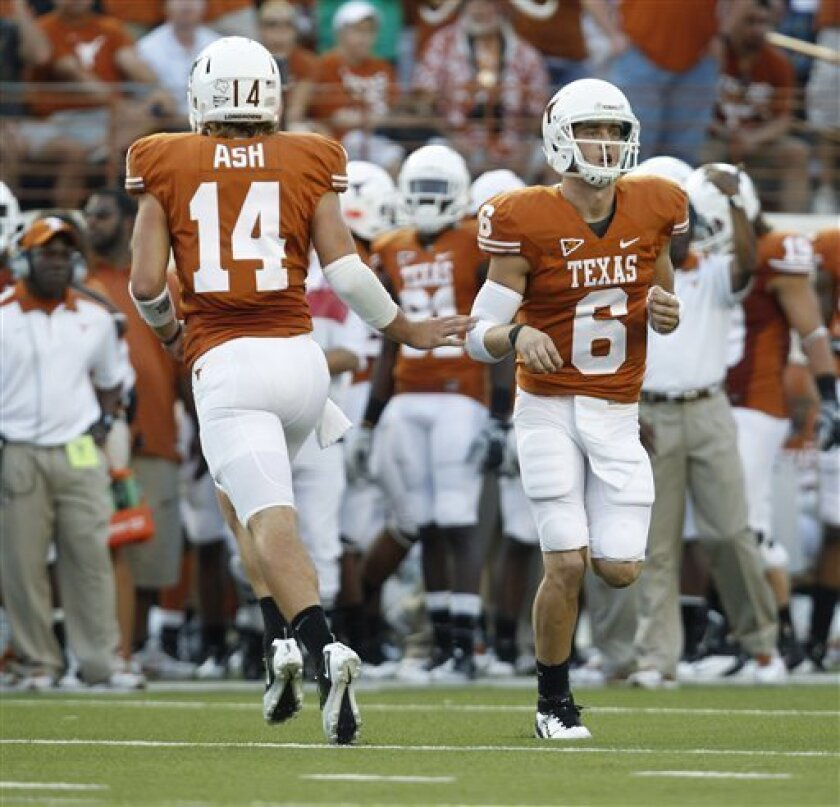 FILE - This Sept. 10, 2011 file photo shows Texas quarterbacks David Ash (14) and Case McCoy (6) passing during the first quarter of an NCAA college football game against BYU, in Austin, Texas. The quickest way to win the hearts of Longhorns fans is to beat the Sooners. Case McCoy and David Ash will get their first chance to do that on Saturday when No. 11 Texas (4-0, 1-0 Big 12) and No. 3 Oklahoma (4-0, 1-0) clash. (AP Photo/Eric Gay, File)