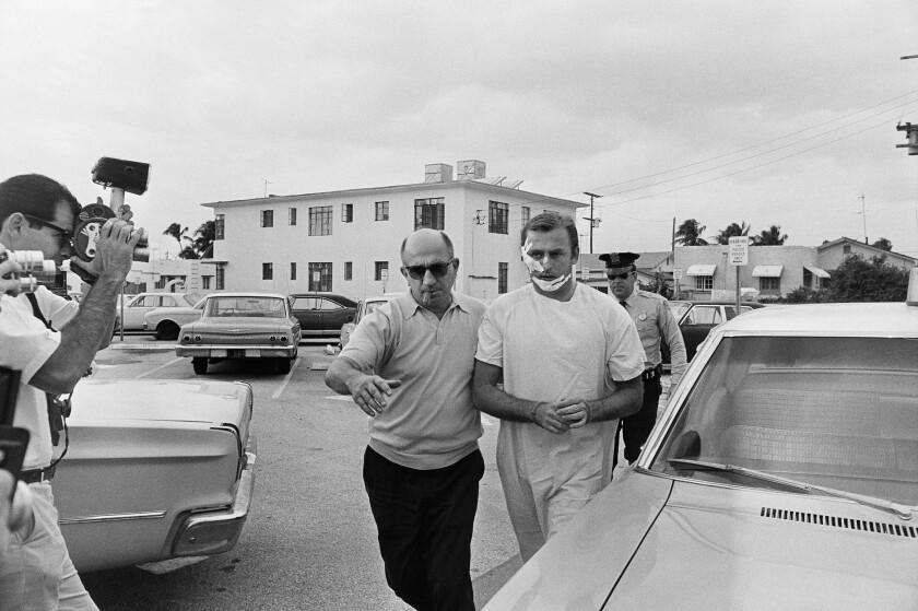 "Jack ""Murf the Surf"" Murphy is escorted into Miami Beach, Fla., police headquarters by a detective in 1968."