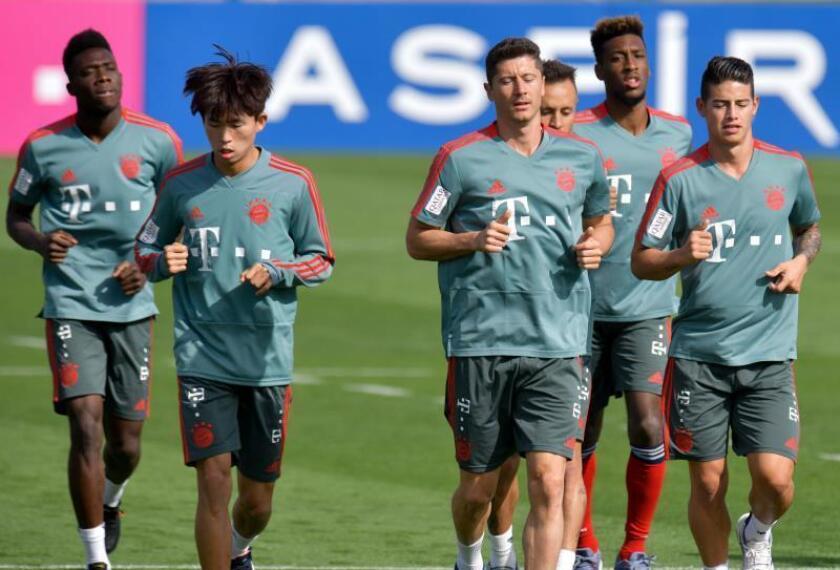 El centrocampista colombiano James Rodríguez (d) calienta junto a Robert Lewandowski (c) y otros compañeros durante un entrenamiento. EFE