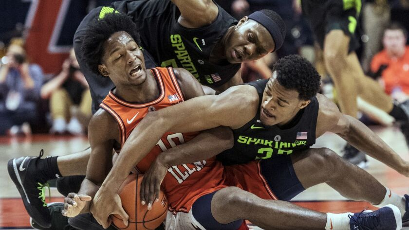 Illinois guard Andres Feliz (10) tries to secure the ball near Michigan State guard Cassius Winston
