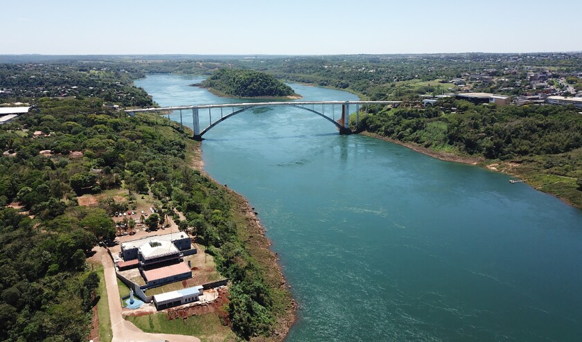 The Friendship Bridge spans over the Parana river along the border of Brazil, right, with Paraguay, left, Wednesday, Oct. 13, 2021. The gigantic Itaipu hydroelectric dam straddling the Brazil-Paraguay border is feeling the heat of Brazil's worst drought in nine decades, with power output at its lowest level since 1994. (AP Photo/Emilio Sanabria)
