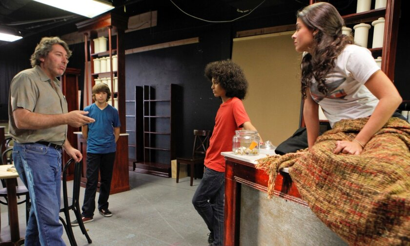 """Director David Ellenstein (far left) works with actors Aaron Acosta, David Michael Coffey and Maritxell Carrero (left to right) during a rehearsal of """"Becoming Cuba"""" at North Coast Repertory Theatre."""