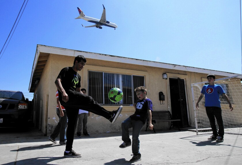 A plane flies overhead as Joe Mejia, 21, left; Derick Montes, 6; and Leonardo Armenia, 14, play in Lennox. A new study has found high levels of potentially harmful particles in communities up to 10 miles east of LAX.