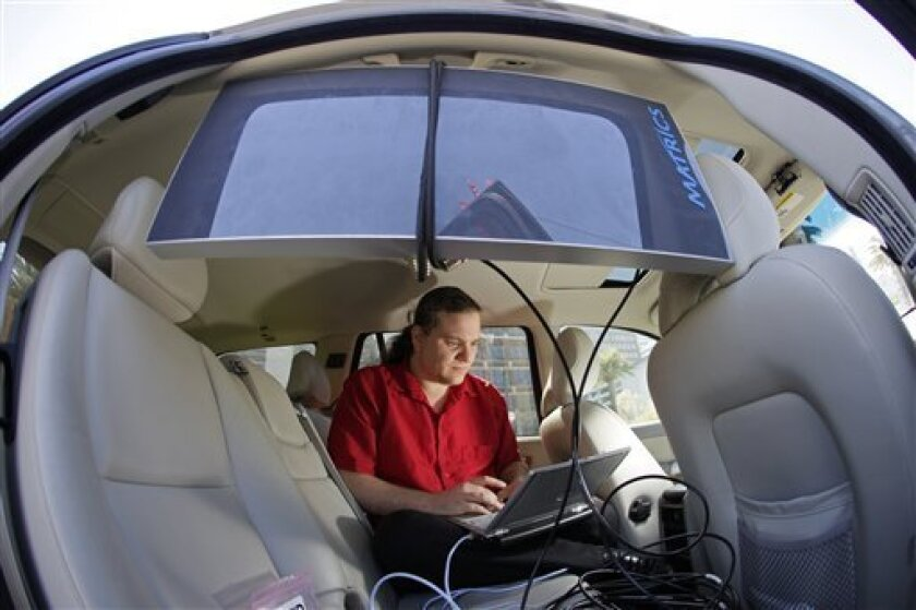 "In this April 10, 2009. photo, Chris Paget, a self-described ""ethical hacker,"" sits in the back of his car with electronic equipment seeking information from imbedded radio frequency identification, or RFID chips as people pass him along the Embarcadero in San Francisco. (AP Photo/Eric Risberg)"
