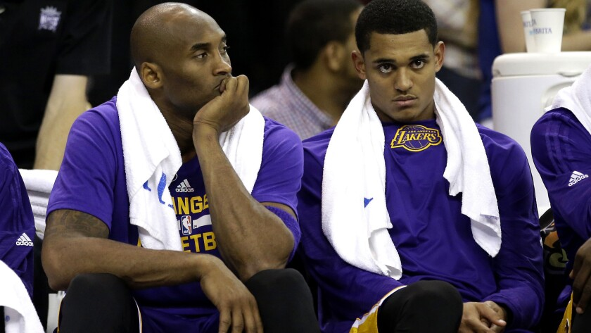 Lakers guards Kobe Bryant, left, and Jordan Clarkson rest on the bench during the second half of their game against the Kings on Friday night.