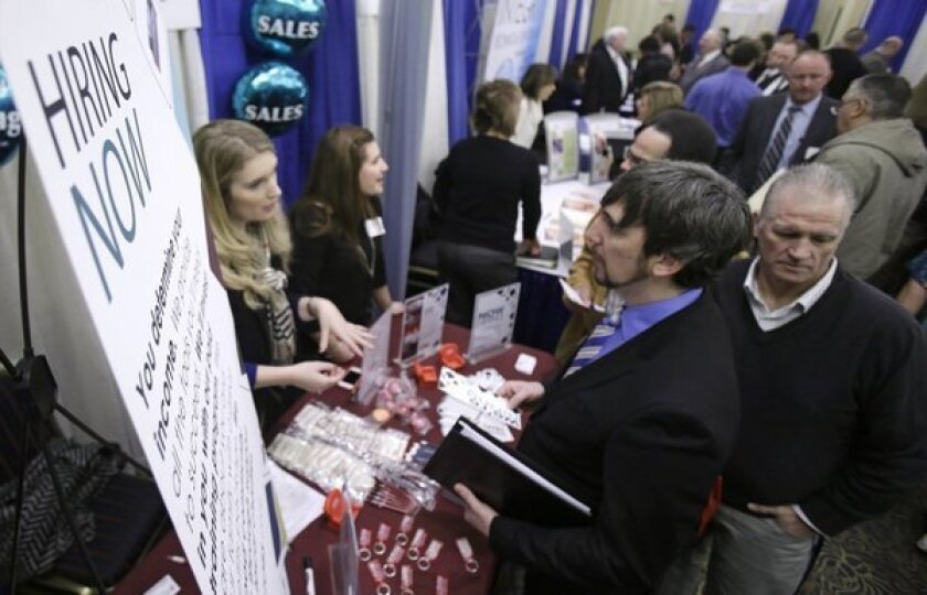 Job seekers talk with employers during a job fair this year in Cuyahoga Falls, Ohio.