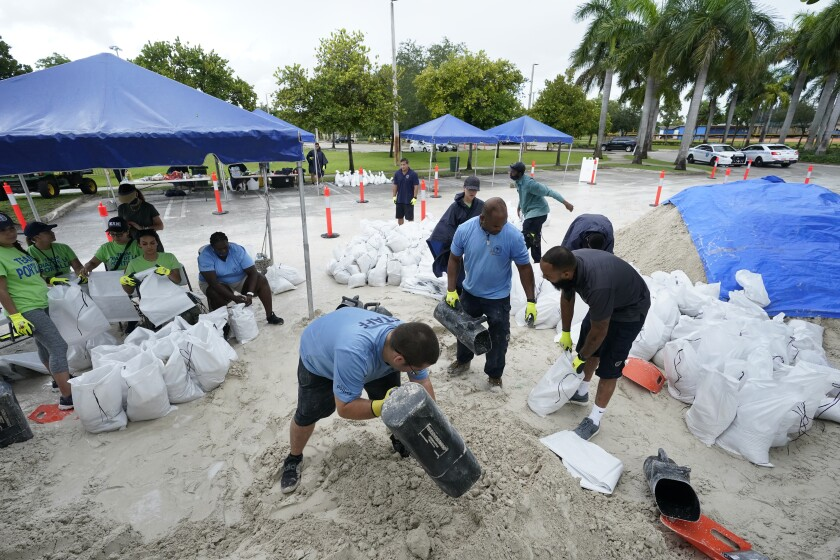 City workers fill sandbags at a drive-thru sandbag distribution event for residents ahead of the arrival of rains associated with tropical depression Fred, Friday, Aug. 13, 2021, at Grapeland Park in Miami. Forecasters say tropical depression Fred is slowly strengthening and could regain tropical storm status Friday. (AP Photo/Wilfredo Lee)