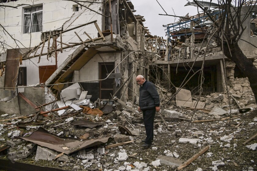 An elderly man stands in front of a destroyed house after shelling between Armenia and Azerbaijan over the disputed region.