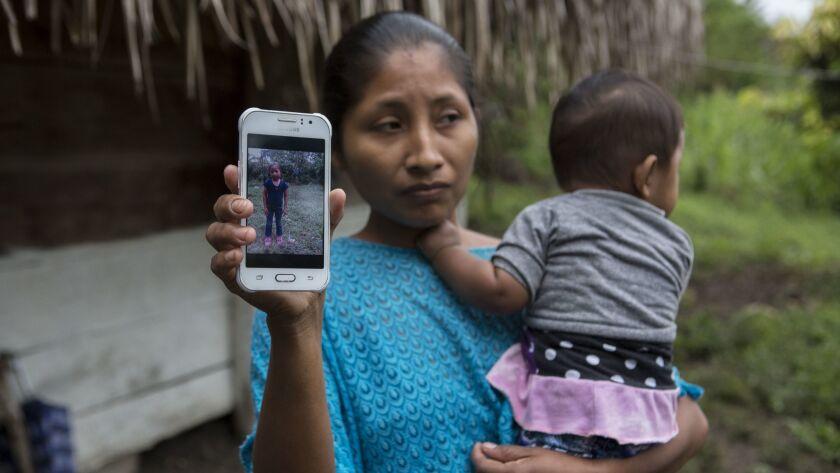 Claudia Maquin, 27, shows a photo of her daughter, Jakelin Amei Rosmery Caal Maquin in Raxruha, Guat