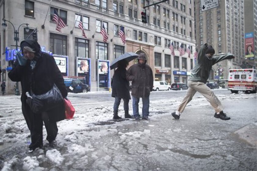 Pedestrians attempt to traverse slush puddles near Pennsylvania Station in New York.