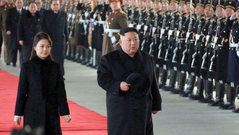 North Korean leader Kim Jong Un walks with his wife Ri Sol Ju at Pyongyang Station in Pyongyang, North Korea, before leaving for China on Monday.