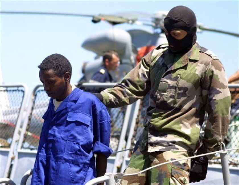 A masked French soldier escorts an alleged pirate on the French naval frigate, Nivose, as the ship docked at the Mombasa port in Kenya Friday, May 8, 2009 . Eleven suspected Somali pirates alleged to have mistakenly attempted to hijack a French naval ship on May 3 have Friday been handed over to Kenyan authorities.(AP Photo/Str)