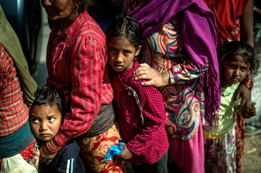 Victims of the Nepal earthquake line up along a road as they wait to receive food and goods at an aid distribution point in Bhotechaur on Friday.