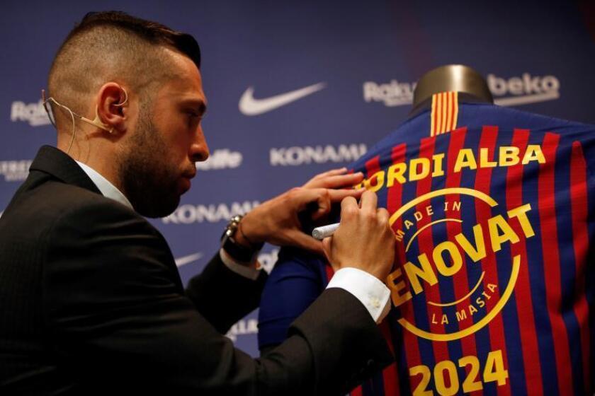 El defensa del Barcelona Jordi Alba firma una camiseta durante el acto de renovación de su contrato con el FC Barcelona hasta junio de 2024 que se ha escenificado este lunes en el Camp Nou. EFE