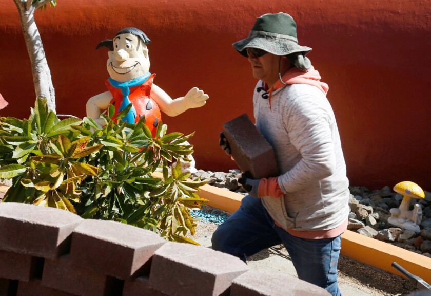A landscaper passes a Fred Flintstone statue while working at the home in Hillsborough.