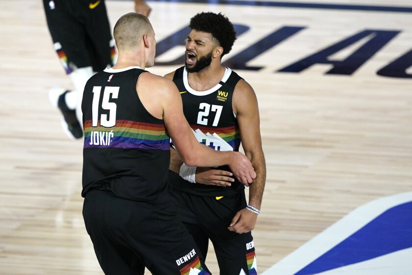 Nuggets guard Jamal Murray (27) and center Nikola Jokic (15) celebrate during their overtime defeat of the Jazz on Monday.