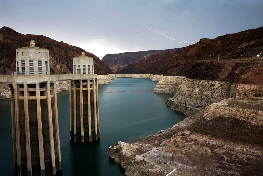 FILE - In this July 28, 2014, file photo, lightning strikes over Lake Mead near Hoover Dam that impounds Colorado River water at the Lake Mead National Recreation Area in Arizona. The Bureau of Reclamation is forecasting first-ever water shortages because of falling levels at Lake Mead and says the reservoir could drop so low that it might not be able to generate electricity at Hoover Dam. (AP Photo/John Locher, File)