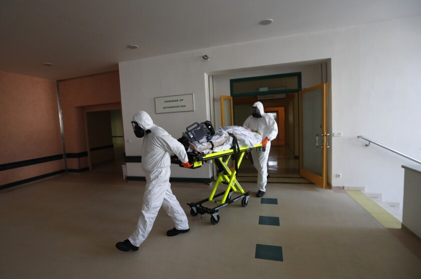 Health care workers transport a COVID-19 patient from an intensive care unit (ICU) at a hospital in Kyjov to hospital in Brno, Czech Republic, Thursday, Oct. 22, 2020. With cases surging in central Europe, some countries are calling in soldiers, firefighters, students and retired doctors to help shore up buckling health care systems. Many faced a shortage of medical personnel even before the pandemic, and now the virus has sickened many health workers, compounding the shortfall. (AP Photo/Petr David Josek)