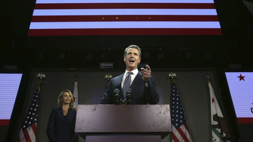 Gov.-elect Gavin Newsom addresses the crowd at an election-night party on Nov. 6 as his wife, Jennifer Siebel Newsom, left, looks on.