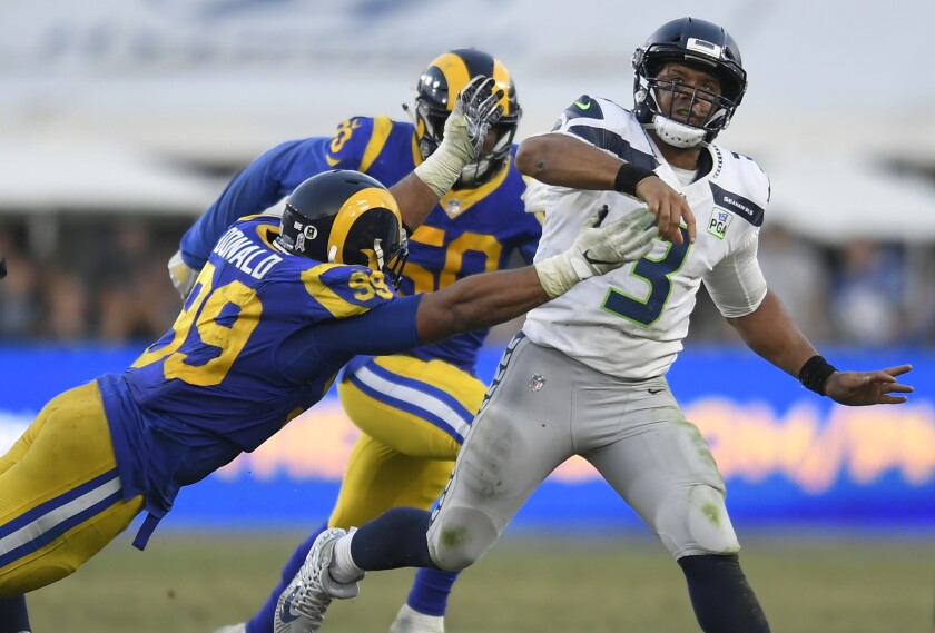 Seattle's Russell Wilson gets off a pass before the Rams' Aaron Donald can tackle the quarterback in an NFC West battle last season.