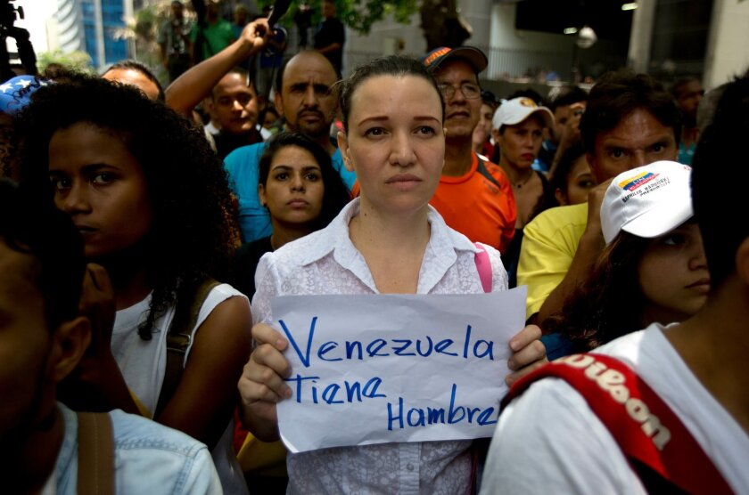 "An opposition members holds a handwritten message that that reads in Spanish; ""Venezuela is hungry,"" during a protest outside the court offices of the Chacao municipality, in Caracas, Venezuela, Wednesday, May 25, 2016. Opposition members held a demonstration to demand authorities hold a recall ref"