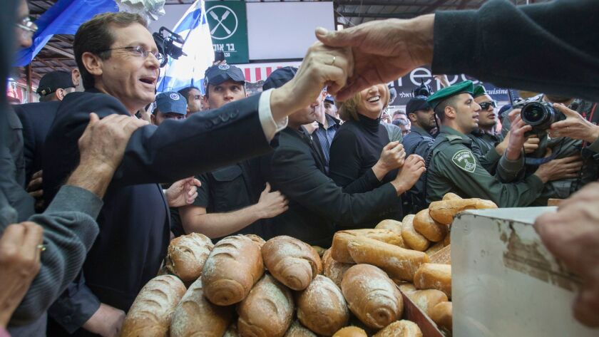 In this March 12, 2015, file photo, Israeli Labor party leader Isaac Herzog, left, visits a market in Tel Aviv.