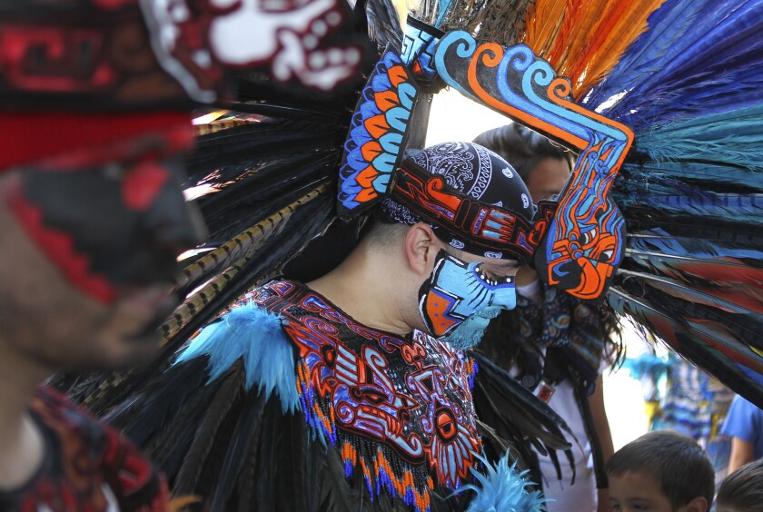 Chicano Park celebrated its historic designation with the 43 anniversary of the park in 2013. Juan Flores of the group Callpulli Mexica, dressed in Aztec apparel with facepaint and feathers adjusts his headdress during the celebration.