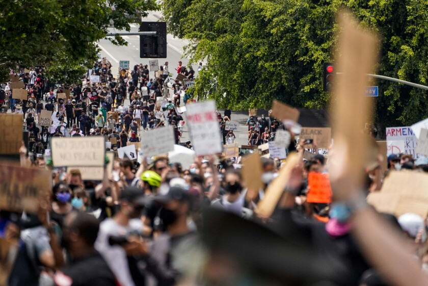 Demonstrators walk down First Street toward LAPD headquarters June 2 in Los Angeles.