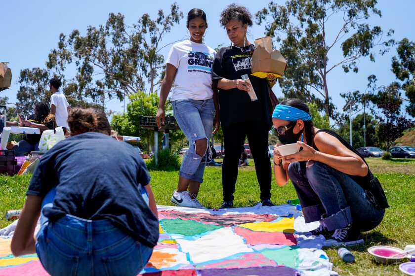 Melina Abdullah chats with her daughter while looking at a banner being painted at a Black Lives Matter event