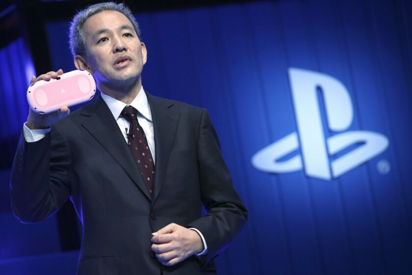 """Sony Computer Entertainment Japan and Asia (SCEJA) President Atsushi Morita reveals a """"Light Pink/White"""" model of the PlayStation Vita during SCEJA press conference in Tokyo, Monday, Sept. 1, 2014. (AP Photo/Eugene Hoshiko)"""