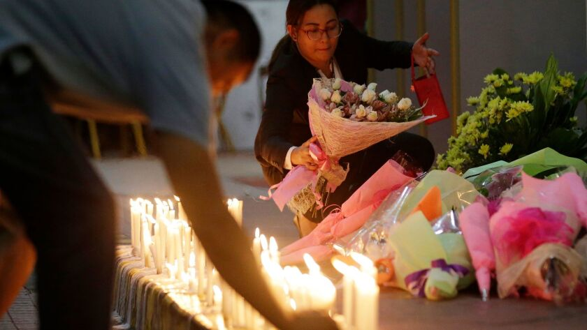 Mourners offer candles and flowers for victims of an attack at the Resorts World Manila complex, Fri