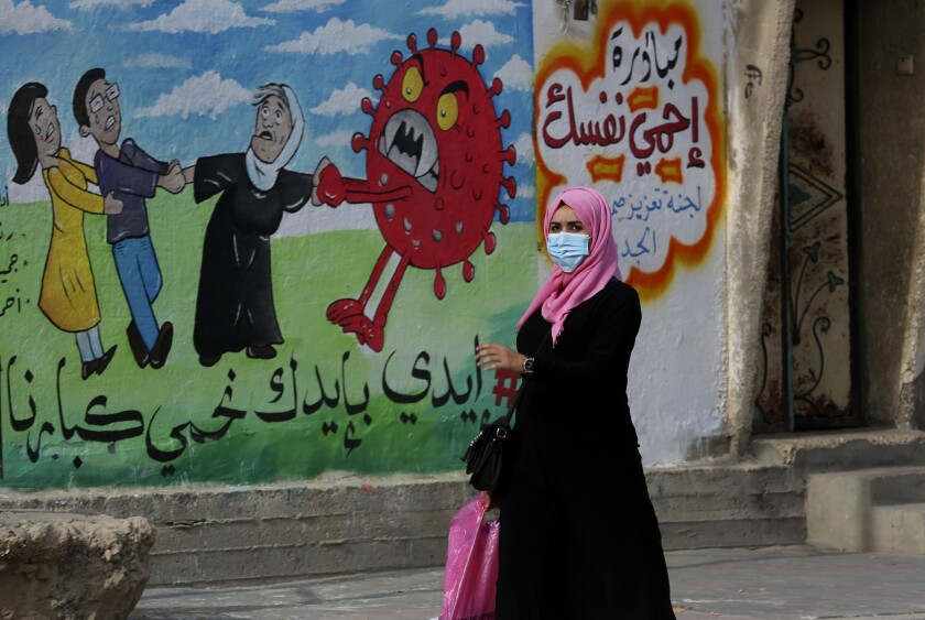 """FILE - A woman walks past a mural encouraging the wearing of face masks amid the coronavirus pandemic, on the main road of Nusseirat refugee camp, central Gaza Strip, on Nov. 24, 2020. Arabic reads: """"protect yourself, together we protect the old."""" The prickly orb is on every news and medical site. It's all over TV and on flyers for COVID car cleaning. (AP Photo/Adel Hana, File)"""