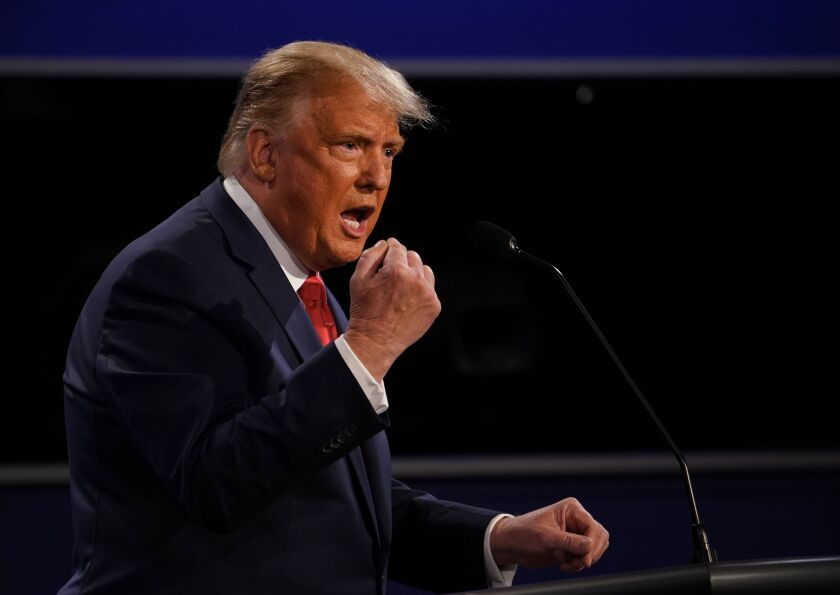 President Trump curls his right hand into a fist while speaking onstage at the debate