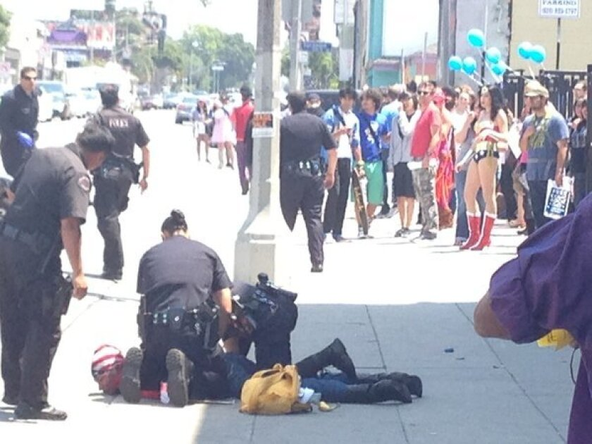 In front of Golden Apple Comics on Free Comic Book Day, LAPD officers arrest a woman they say fled the scene of a hit-and-run.