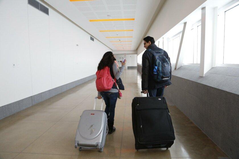 Travelers walk across the new bridge linking San Diego with the Tijuana airport.