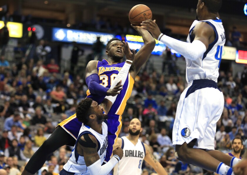 Lakers forward Julius Randle tries to score inside against Mavericks guard Wesley Matthews and forward Harrison Barnes, right, during the first half Sunday.