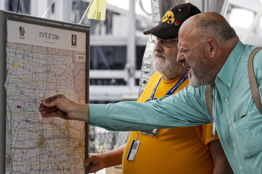 Clifford d'Autremont, from Davenport, Iowa, left, watches William Weldon place a thumb tack on Iowa Falls on the map of Iowa.