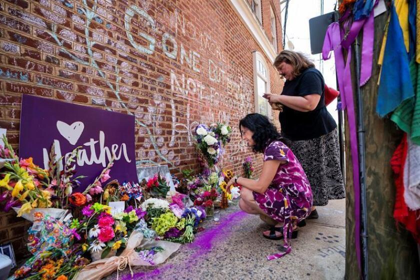 Varias mujeres colocan flores en el memorial de Heather Heyer, una mujer de 32 años atropellada en ese lugar por un supremacista en una contraprotesta en 2017, en Charlottesville, Virginia (Estados Unidos). EFE/Archivo